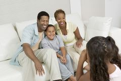 Girl Taking Picture of Family on sofa. In living room Royalty Free Stock Photo