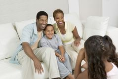Girl Taking Picture of Family on sofa in living room Royalty Free Stock Image