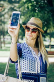 Girl taking a picture of herself outdoor. Girl smiling while taking a picture of herself outdoor Royalty Free Stock Image