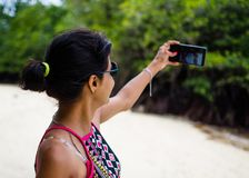 Girl Taking a Picture of Self on a Beach royalty free stock photo