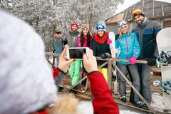 Girl taking pictures of cheerful friends on cold winter day Royalty Free Stock Photos