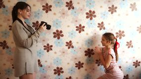 Girl taking pictures of a little girl. On a black camera stock video