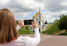 Girl taking pictures on mobile smart phone. In front view Temple in the town of Dmitrov Royalty Free Stock Images