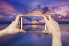 Girl taking pictures on mobile smart phone in sunset beach,Phuke Stock Images