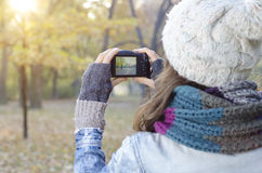 Girl taking pictures in the park Stock Photography