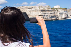 Girl taking pictures on a phone in Bonifacio, Royalty Free Stock Images