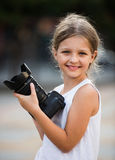 Girl taking pictures with professional camera outdoors Stock Image