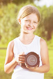 Girl taking pictures with professional camera outdoors Royalty Free Stock Photography