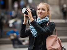 Girl taking pictures of sights at city excursion Royalty Free Stock Photos