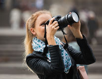 Girl taking pictures of sights at city excursion Royalty Free Stock Image