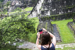 Girl taking pictures in Tikal royalty free stock photo