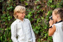 Girl taking pictute of boy outdoors. Stock Photography