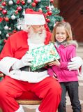 Girl Taking Present From Santa Claus Stock Images