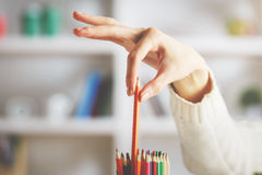 Girl taking red pencil. Close up of girl`s hand taking red pencil out of holder on blurry shelf background Stock Photo
