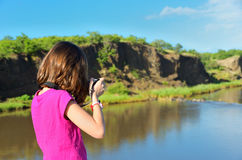 Girl taking river photo by camera Stock Photo