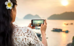 Girl taking seaside sunset picture with smartphone Stock Images