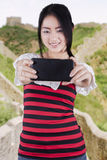 Girl taking self portrait at Great Wall of China Stock Photography