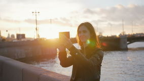 A girl taking selfie as the sun sets in a wonderful place. Busy road, a bridge, a river at the background, slow mo. Amazing view of a girl taking selfie at the stock video footage