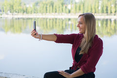Girl taking a selfie. A beautiful young girl taking a selfie with a cellphone Stock Photography