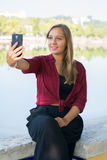 Girl taking a selfie. A beautiful young girl taking a selfie with a cellphone Stock Photo