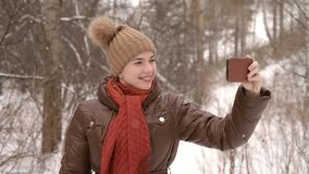Girl taking a selfie with a big smile. Girl taking a selfie in a winter forest with a smartphone stock footage