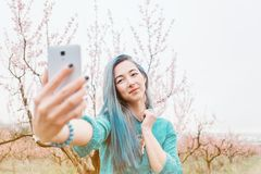 Girl taking selfie in blossoming garden. royalty free stock photography