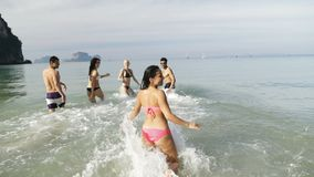 Girl Taking Selfie Of Cheerful People Running In Water On Beach, Happy Young Man And Woman Group Having Fun. Slow Motion 120 stock footage