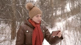 Girl taking a selfie in a forest. Girl taking a selfie in a winter forest with a smartphone stock footage
