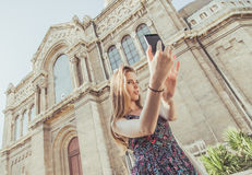 Girl taking selfie in front of palace Stock Images