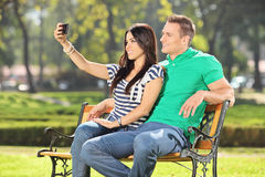 Girl taking a selfie with her boyfriend in park Royalty Free Stock Photography