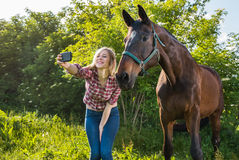 Girl taking a selfie. With his horse royalty free stock image