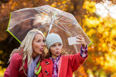 Girl taking selfie with mother at park. Happy girl taking selfie with mother at park during autumn Royalty Free Stock Image