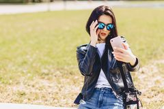Girl taking selfie on phone and smiling royalty free stock photography