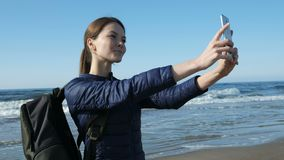 Girl taking selfie at phone on the spring beach. One young 30s hipster positiv lady with rucksack smile and take a photography of empty sunny waterline and her stock video footage