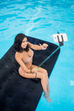 Girl taking selfie photo on the phone with selfie stick and showing thumbs up gesture of good class on mattress in pool royalty free stock photos