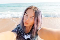 Girl taking selfie on sand beach. royalty free stock photography