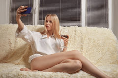 Girl taking selfie. Sensual girl sitting on sofa and taking selfie Royalty Free Stock Images