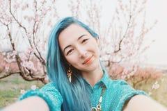 Girl taking selfie in spring garden. royalty free stock image