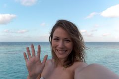 Cheerful young woman in honeymoon greeting her friend. Sea as Background royalty free stock photo