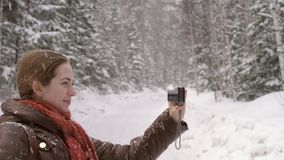 Girl taking a selfie under the snow. In a winter forest stock video