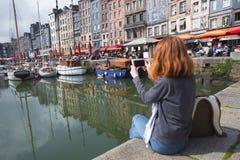 Girl taking a shot of Honfleur harbor Stock Photo