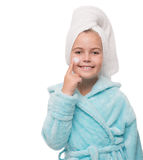 Girl after taking a shower is applying cream on her face. Portrait of cheerful little girl after taking a shower is applying cream on her face Stock Photos