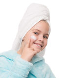 Girl after taking a shower is applying cream on her face. Portrait of cheerful little girl after taking a shower is applying cream on her face Stock Photography