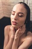 Girl taking shower. Beautiful naked young woman is taking shower in bathroom Royalty Free Stock Image