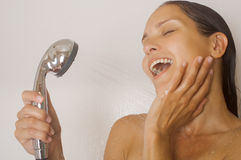 Girl taking a shower and singing. Close up, on a white background Royalty Free Stock Photo