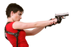 Girl taking sight. Young brunette girl in red tee-shirt and with holster on her back holding air pistol Royalty Free Stock Photo