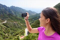 Girl taking smartphone picture of mountain nature Stock Photos