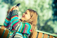 Girl Taking Smartphone Pictures. Happy Teenage Girl Taking Pictures Using Her Modern Smartphone Device Royalty Free Stock Image