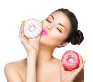 Girl taking sweets and colorful donuts Stock Images