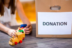 Girl taking toy for donation Royalty Free Stock Images